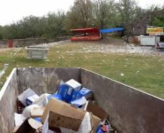 Contenedores medio vacíos y mucha basura esparcida en la pradera